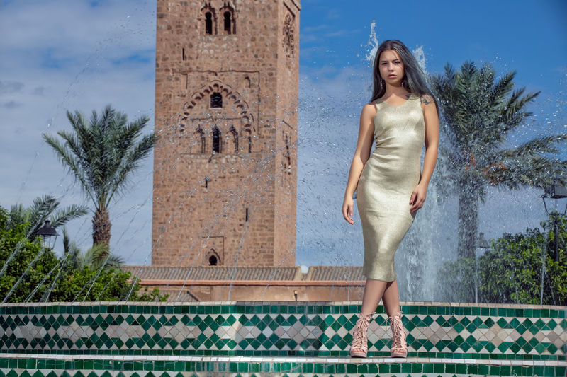 Portrait Of Young Woman Standing Against Fountain