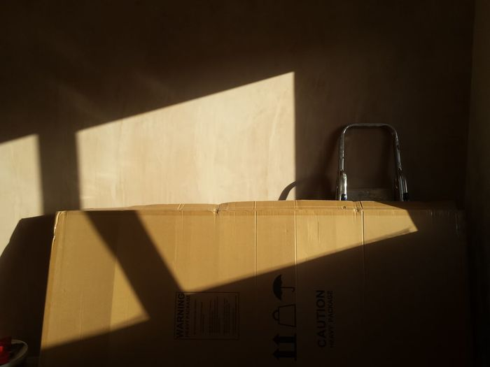 Close-up of cardboard box against wall