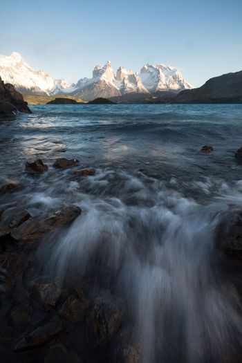 Waves crashing in Torres Del Paine Mountain Scenics Beauty In Nature Nature Sea Water Beach Mountain Range Tranquil Scene Tranquility Landscape Travel Destinations Outdoors No People Sky Day Clear Sky Cold Temperature Winter Wave