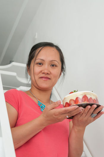 Portrait Of Mid Adult Woman Holding Strawberry Cake By Wall At Home