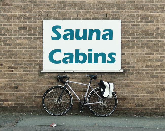 Bicycle parked below sign on wall