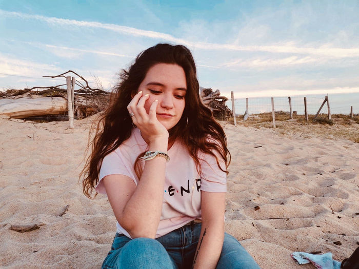 Beautiful young woman sitting on sand at beach against sky