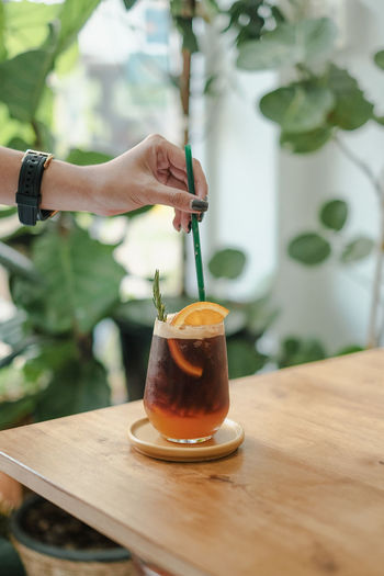 Midsection of person holding yuzu ice americano on table