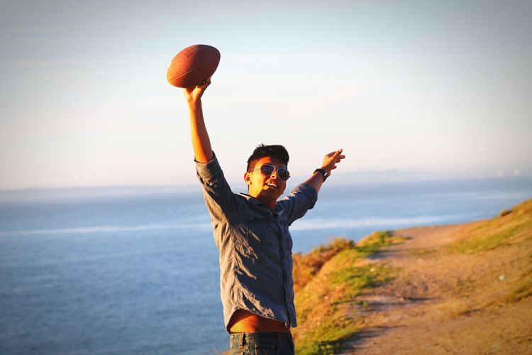 Young man with arms outstretched holding ball against sea