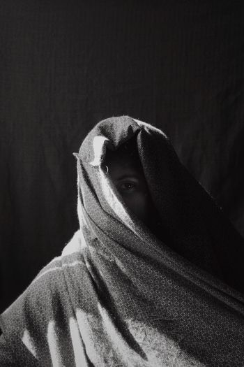 Portrait of man covering face against black background