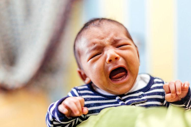 Close-Up Of Baby Crying At Home