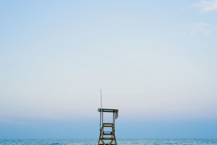Lifeguard hut by sea against clear sky