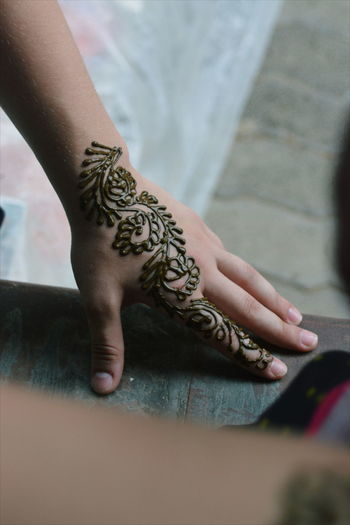 Close-Up Of Woman With Henna Tattoo On Hands