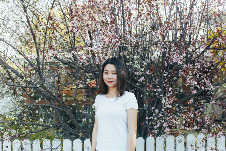 Beautiful Woman Casual Clothing Cherry Blossom Cherry Tree Day Flower Flowering Plant Front View Growth Hair Hairstyle Long Hair Looking At Camera Nature One Person Outdoors Plant Portrait Springtime Standing Tree Women Young Adult Young Women