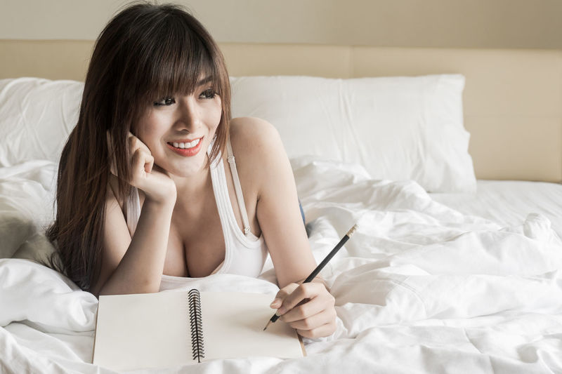 Young Woman Writing While Lying On Bed At Home
