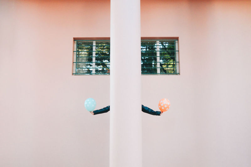 Person Holding Balloons While Hiding Behind Column