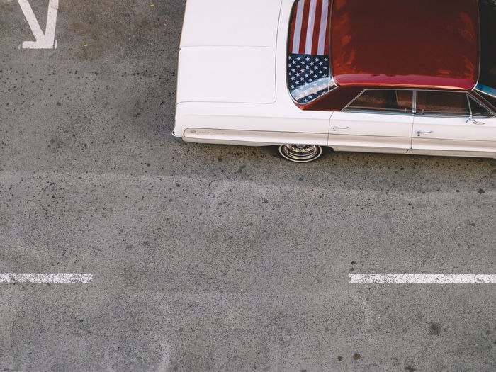 I'm With Her Asphalt Car Chevrolet The Drive Flag High Angle View Land Vehicle Mode Of Transport No People Outdoors Parking Parking Lot Road Stars And Stripes Stationary Street Streetphotography Transportation Travel United States Vintage CarVintage Cars White Fresh on Market 2016 The Street Photographer - 2017 EyeEm Awards Mobility In Mega Cities