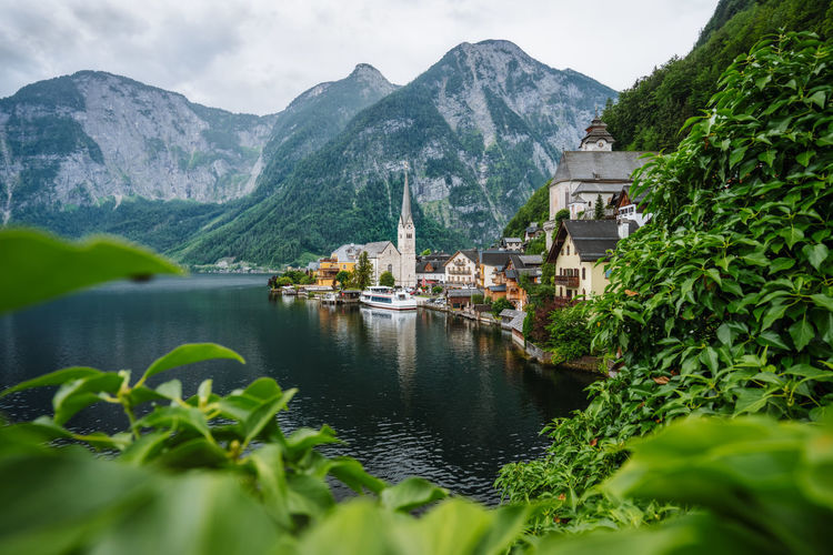 Famous lake side view of hallstatt village with alps behind, foliage leaves framed. austria