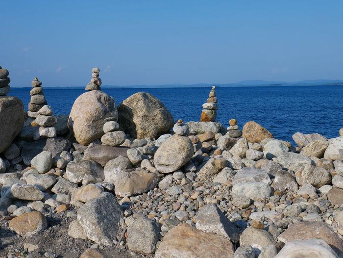 Rocks on beach against blue sky