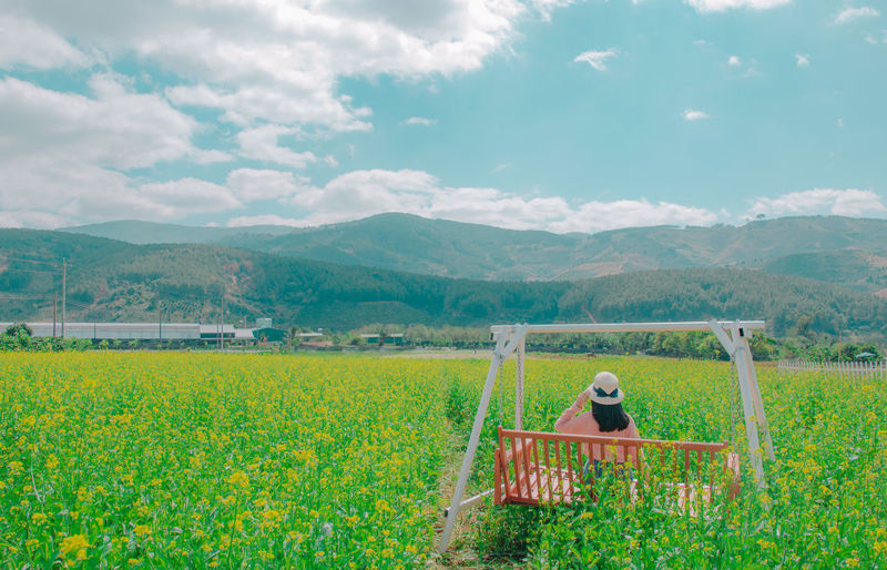 Woman Sitting On Bench Over Field Against Sky