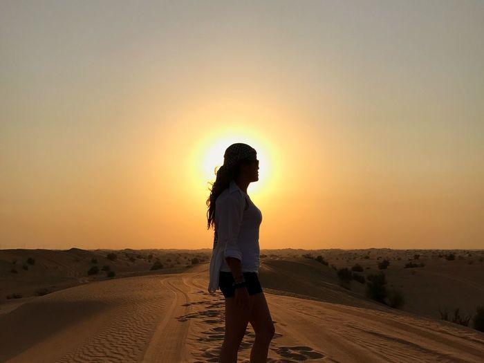 Woman standing on desert during sunset