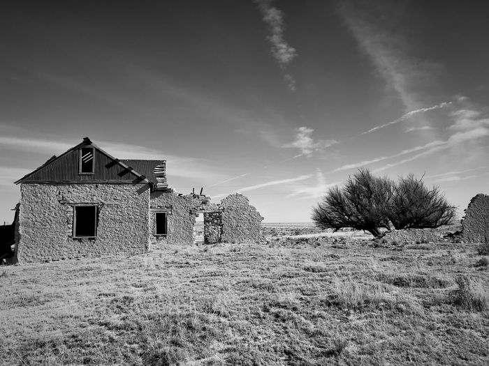 """Mystery Ranch"" For over four years I have driven past this abandoned ranch house set back off Highway 42 in New Mexico, always wanting to photograph it. My hesitation was a gated fence onto the private ranch land. Finally on January 2, 2018 I parked my truck at the gate, climbed over it and walked the near mile into the property and shot my long desired series of the ranch dwellings and surrounding area. It's a mysterious set of buildings and inspecting it only made my curiosity grow even more wondering what the story and history behind it was. Thus I've titled the series ""Mystery Ranch."" It includes both black and white interpretation as well as color as the subject demanded both in its varied study. New Mexico Photography New Mexico Abandoned Places Abandoned Buildings Ranch Black And White Photography Black And White Architecture Building Exterior Built Structure Sky No People Field Landscape"