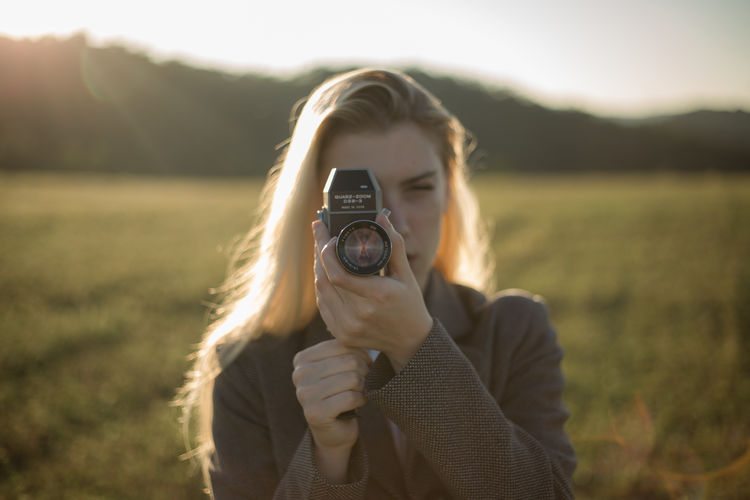 Portrait of young woman photographing outdoors