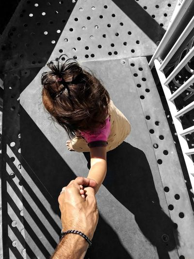 Cropped Image Of Father Holding Daughter Hand On Footbridge