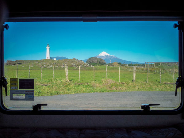 Mount Taranaki and Cape Egmont Lighthouse in New Zealand seen through the window of a touring caravan. Cape Egmont Lighthouse Caravan Landscape Mount Taranaki Mountain New Zealand Sky Sunlight Travel Trailer Vehicle Interior Window