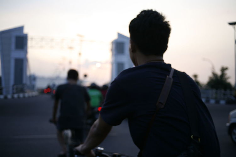 Real People Men Focus On Foreground Architecture Sky City Sunset Rear View Incidental People Lifestyles People Built Structure Building Exterior Nature Leisure Activity Standing Silhouette Street Outdoors Two People Cycling Asian  Java INDONESIA Selective Focus