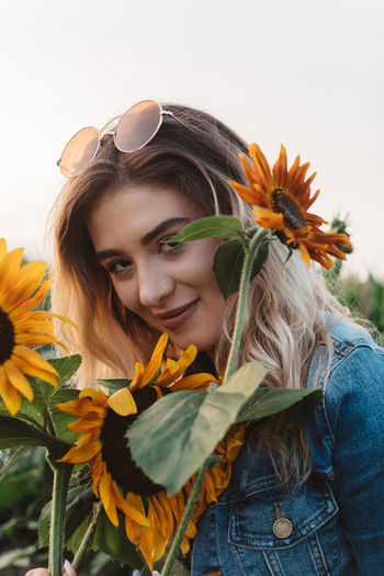 Portrait Of Smiling Young Woman With Sunflowers Against Clear Sky