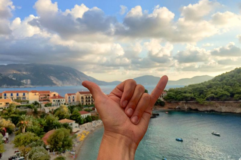 Person gesturing shaka sign by lake against sky