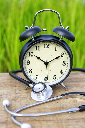 Close-up of stethoscope and alarm clock on table