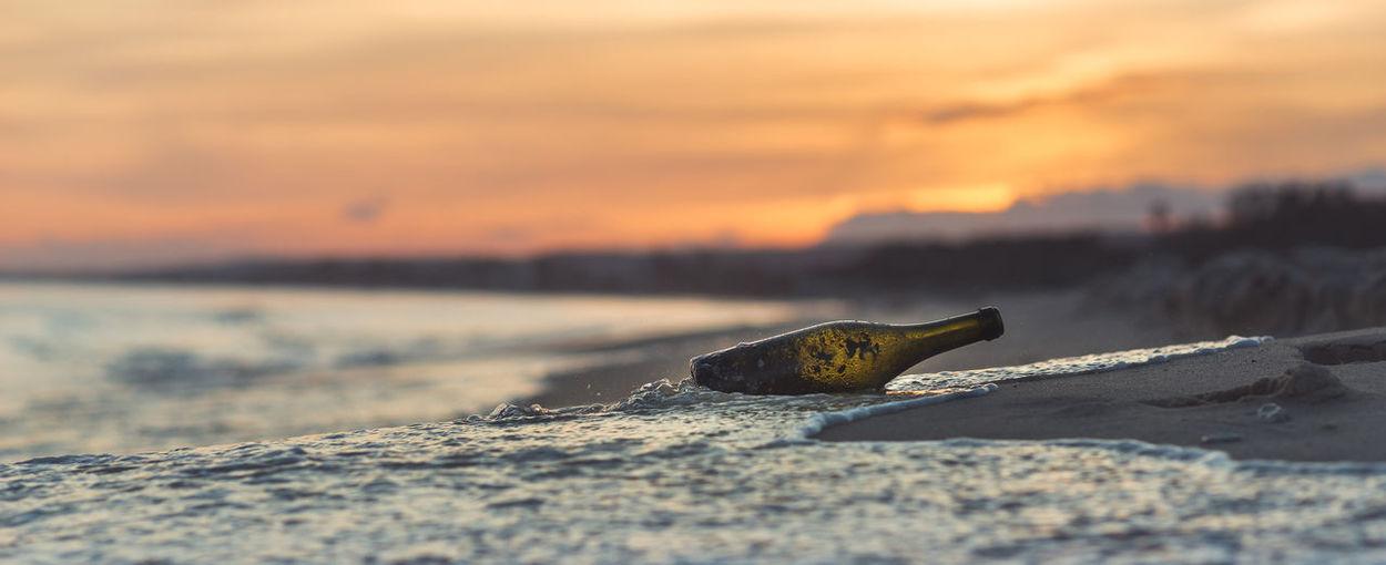 Bottle on beach against sky during sunset