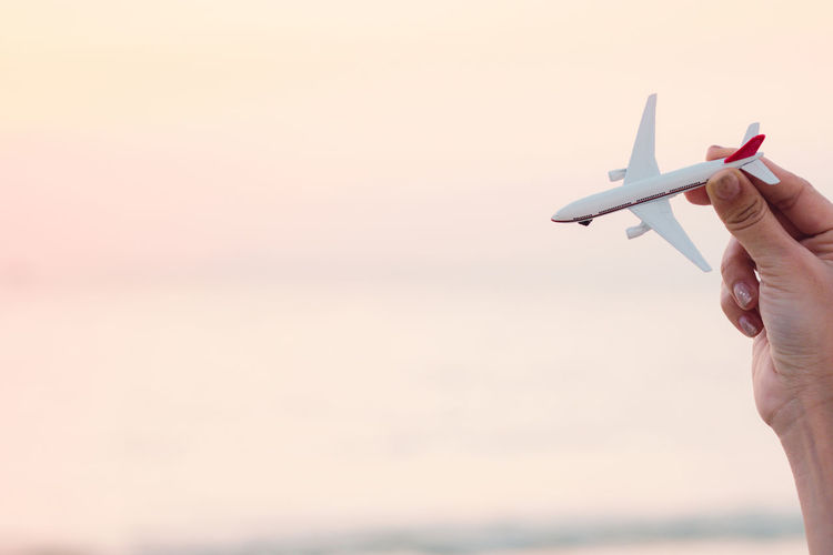 Woman hand holding airplane model in sunset sky and summer sea background dreams of journey in vacation. Travel and air transportation, Passenger plane landing in sunrise, Hand with small toy plane. Landing Transportation Vacations Air Vehicle Airplane Copy Space Finger Flight Focus On Foreground Hand Holding Horizon Over Water Human Body Part Human Hand Journey Leisure Activity Lifestyles Nature Outdoors Sea Sky Summer Sunset Unrecognizable Person Water