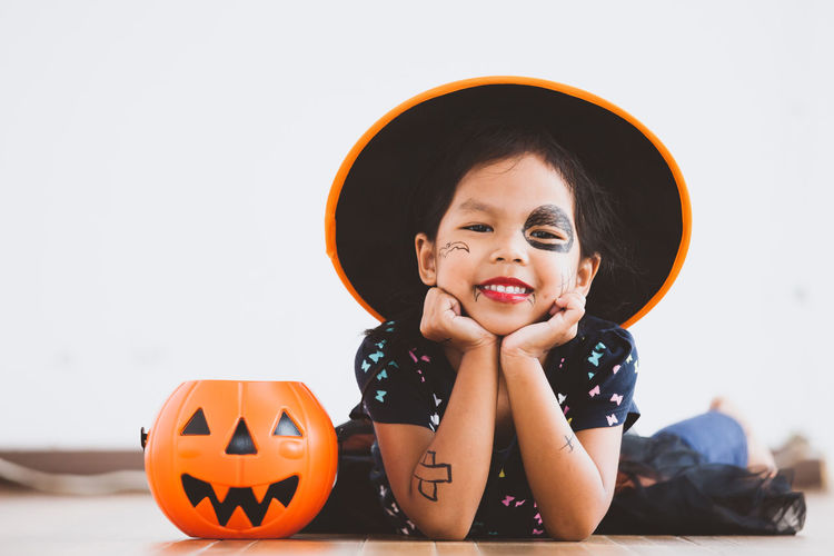 Portrait of cute playful girl with spooky make-up lying on floor at home during halloween