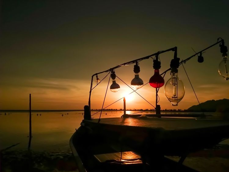 Sunset Boat Bulb Bulbs Light Foreground Boat Silhouette Fisherman Boat Sunset Sky Water Sun Scenics - Nature Nature Silhouette Sea Orange Color Beauty In Nature Non-urban Scene Tranquility Tranquil Scene No People Reflection Cloud - Sky Fishing Industry Outdoors Transportation