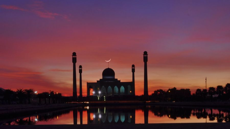 Silhouette Mosque By Lake Against Sky During Sunset