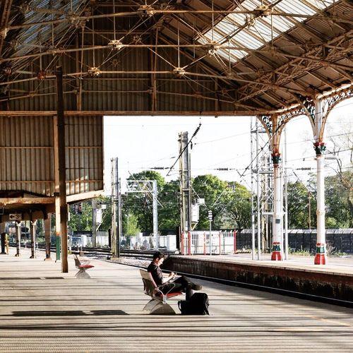 Businessman using cell phone on railway platform