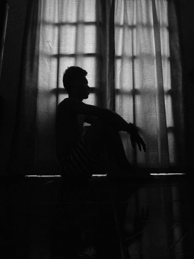 Side view of silhouette man sitting at home