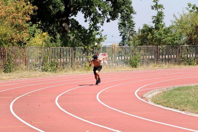 Shirtless man running on track