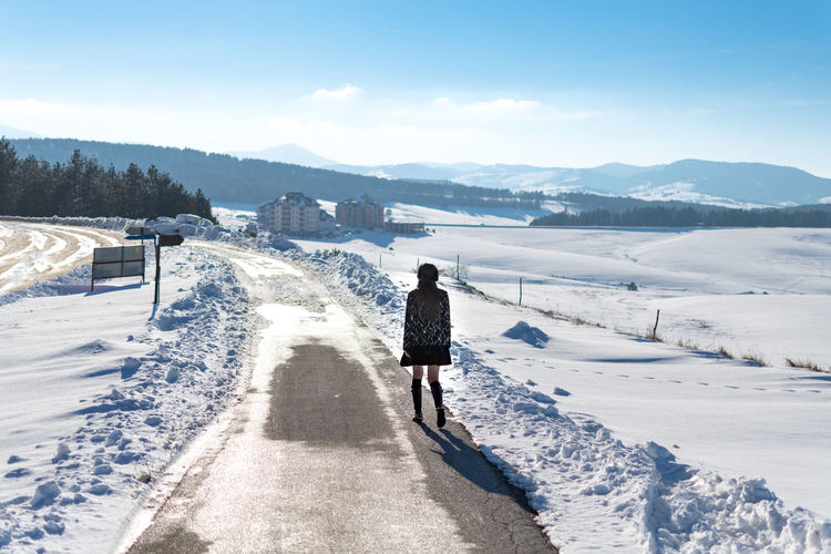 Snow Winter Cold Temperature One Person Real People Rear View Mountain Lifestyles Full Length Leisure Activity Nature Beauty In Nature Day Sky White Color Sunlight Covering Walking Warm Clothing Outdoors Snowcapped Mountain