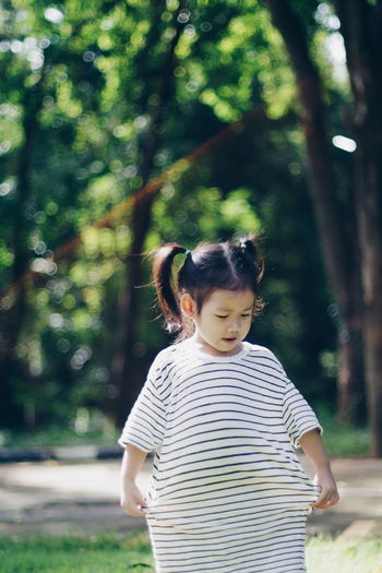The little girl wore his brother's shirt. Casual Clothing Childhood Day Fashionable Focus On Foreground Girl Growth Leisure Activity Lens Flare Lifestyles Nature One Person Outdoors People Real People Standing Striped Top Knot Tree