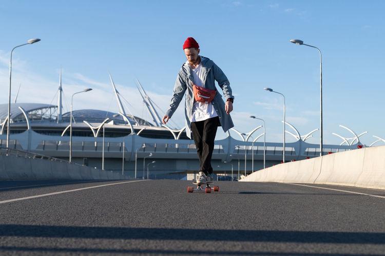 Man skateboarding on road against sky in city