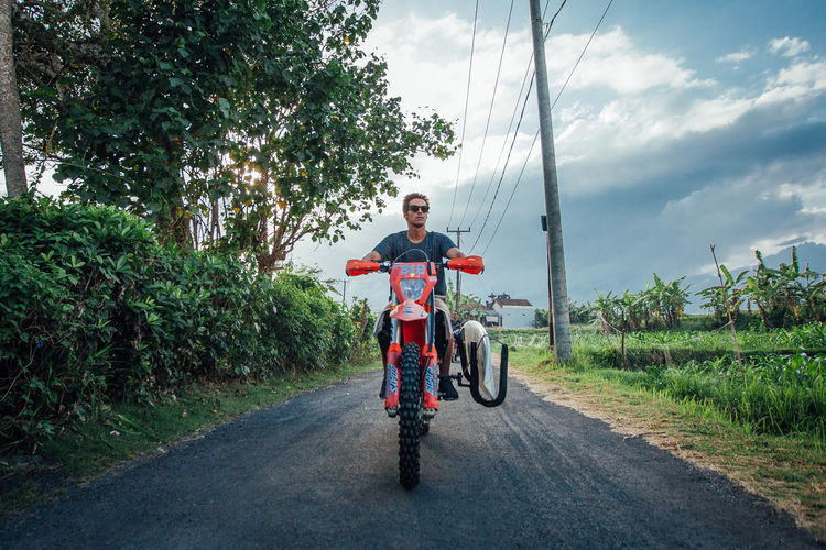 Man riding motorcycle on road against sky