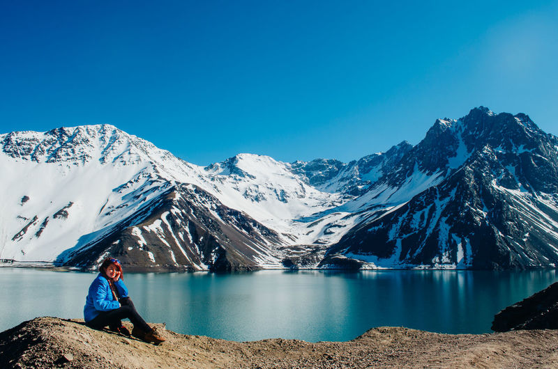 Full length of woman sitting by lake against mountains and sky