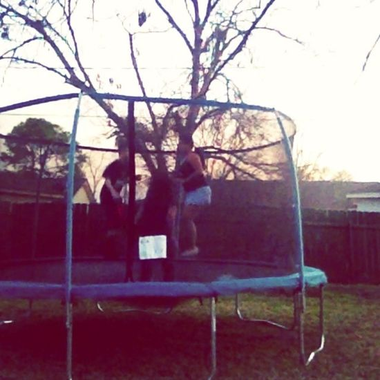 On the trampoline with mommy and brother