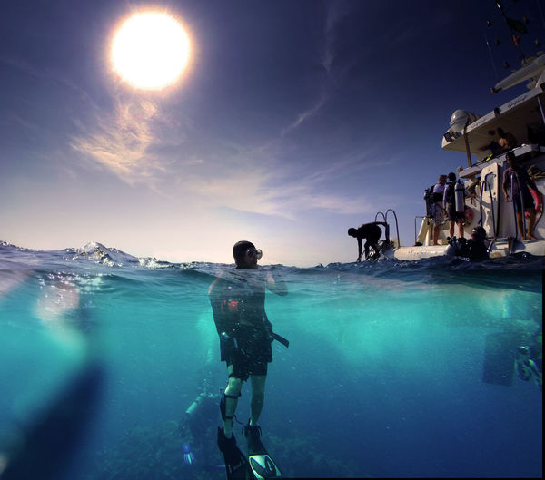 Man scuba diving in red sea against blue sky