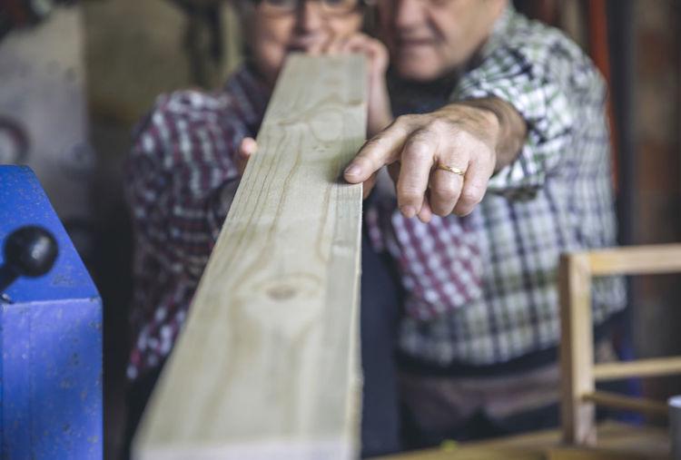 Workers measuring wood in workshop