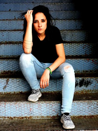 Portrait of young woman sitting on steps