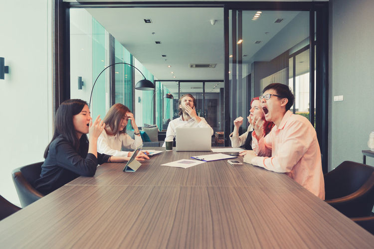 Group of business people yawning in a meeting room, sharing their ideas, Multi ethnic Brainstorming Discussing Business Business Meeting Business People Business Person Businessman Businesswoman Colleague Colleagues Communication Corporate Business Coworker Desk Group Group Of People Indoors  Laptop Meeting Meeting Room Men Multi Ethnic Occupation Office Sitting Table Teamwork Technology Togetherness Western Wireless Technology Women Working