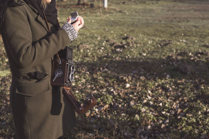 Analogue Photography Adult Camera - Photographic Equipment Communication Day Gun Holding Lifestyles Nature One Person One Woman Only Only Women Outdoors Photographing Photography Themes Real People Shooting A Weapon Standing Technology Village Life Warm Clothing Weapon Women