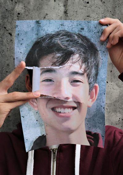 Portrait of smiling boy holding torn self portrait