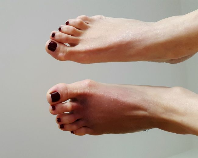 Low Section Of Woman With Feet Up Against Gray Background