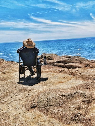 Rearview of man sitting in chair at ocean Cliff's edge. Whale watching. Patience. Man Straw Hat Patience Whale Watching Folding Chair Cliff's Edge Background Sandstone vanishing point Distance Watching Water Sea Sand Sunlight Shadow Sky Horizon Over Water Calm Tranquil Scene Ocean Countryside Mid Distance Headland Seaside Tranquility Idyllic Remote Scenics Cloud The Traveler - 2019 EyeEm Awards The Mobile Photographer - 2019 EyeEm Awards The Great Outdoors - 2019 EyeEm Awards The Minimalist - 2019 EyeEm Awards